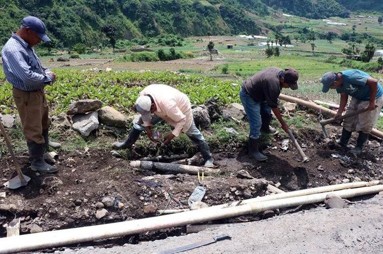 Agricultores reparan tubería de agua para riego en Zunil, Quetzaltenango. (Foto Prensa Libre: Carlos Ventura)