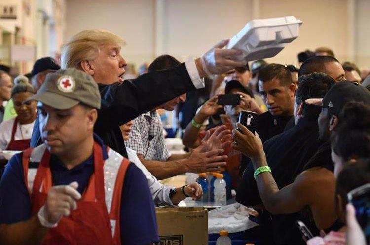 Pareja presidencial entrega alimentos en un refugio a víctimas por paso del Huracán Harvey en Texas.