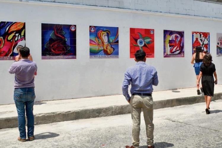 Universitarios aprecian algunas pinturas colocadas en una calle de la ciudad de Retalhuleu.