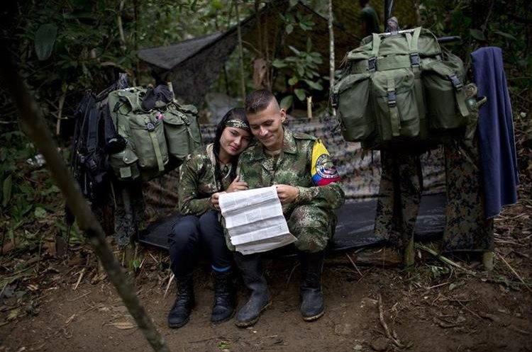 "In this Jan. 4, 2016 photo, Juliana, a rebel soldier of the 36th Front of the Revolutionary Armed Forces of Colombia, or FARC, sits her with boyfriend Alexis, in their makeshift tent, inside their hidden camp in Antioquia, Colombia. ""Inside the guerrilla we don't touch money, everything is given to us, from medicine to cigarettes. That's why there's no dependency in which she expects me to provide for her as is common in Latin America,"" explains Alexis. ""Between us there's just love."" (AP Photo/Rodrigo Abd)"