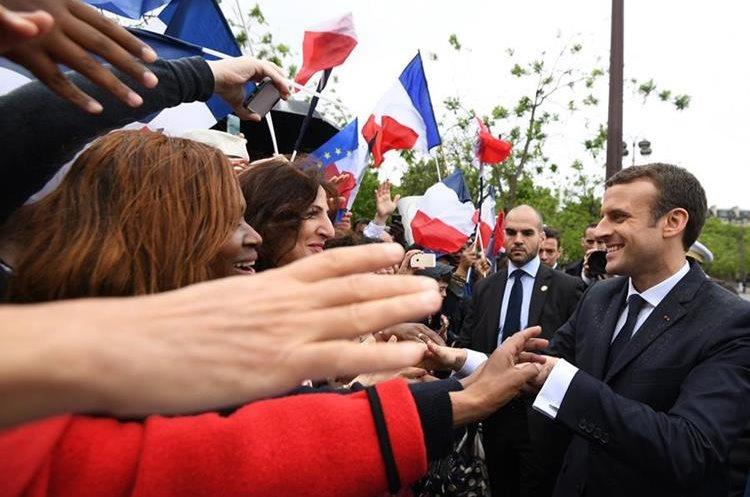 Emmanuel Macron saluda a simpatizantes después de una ceremonia en el Arco del Triunfo.(AP).