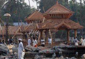 Curiosos observan los daños en el templo de Paravoor. (AP).