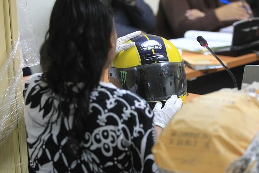 Perito analiza el casco utilizado por los supuestos sicarios que ultimaron a Ingrid Gabriela Conedera Vargas, secretaria de la procuradur'a general de la naci—n (PGN). (Foto Prensa Libre: Esbin Garcia)