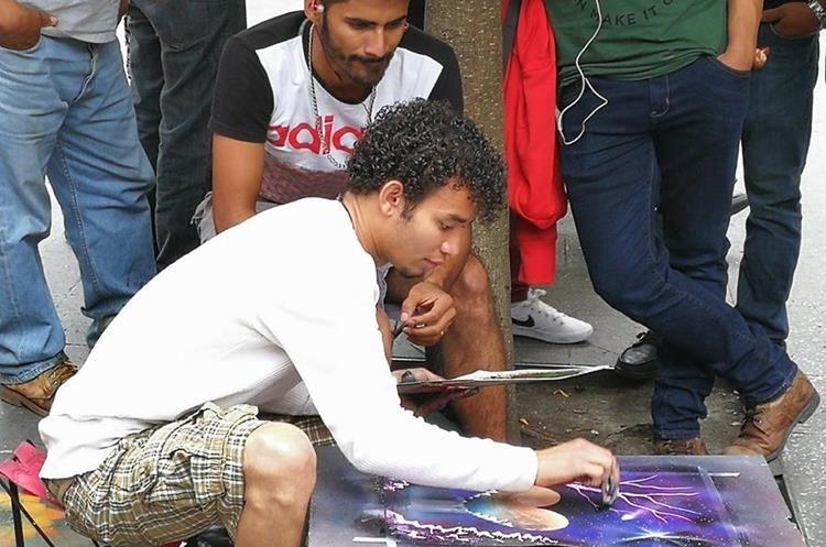 Cristian Sánchez Vigil  observa como  uno de sus compañeros pinta con aerosol, en la Sexta Avenida. (Foto Prensa Libre: César Pérez)