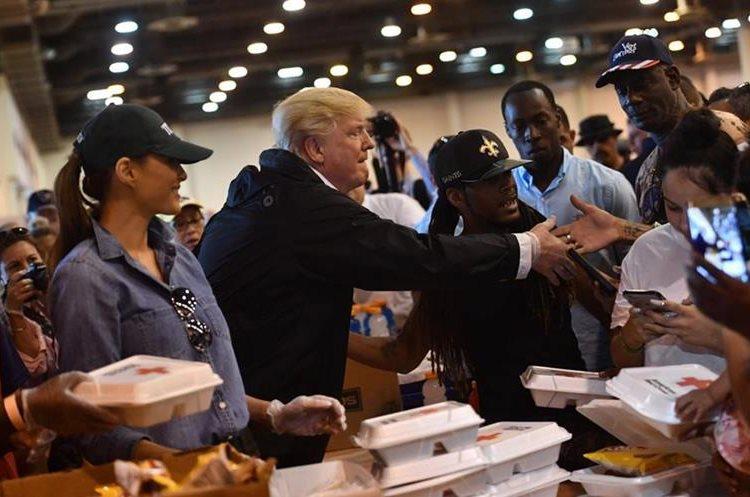 Presidente Donald Trump y la primera dama Melania Trump sirven alimentos en un refugio de Houston, Texas.