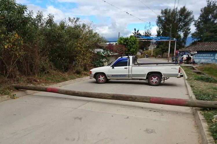 Un poste y un vehículo bloquean uno de los ingresos a San Bartolomé Jocotenango, Quiché. (Foto Prensa Libre: Héctor Cordero)