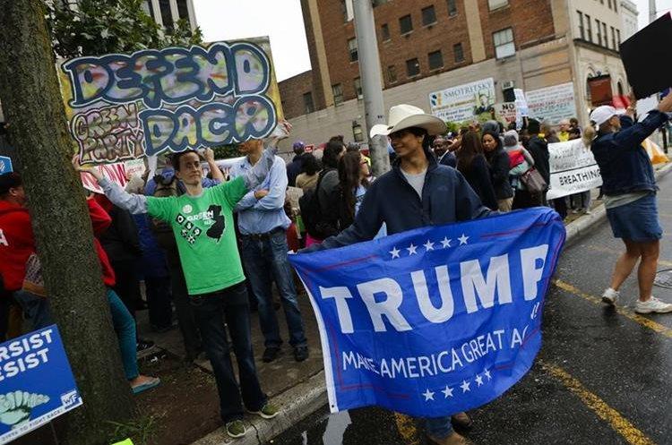 Un partidario de Trump aparece junto a activistas de inmigración protestan contrael fin al programa del DACA en Newark, Nueva Jersey. (AFP).