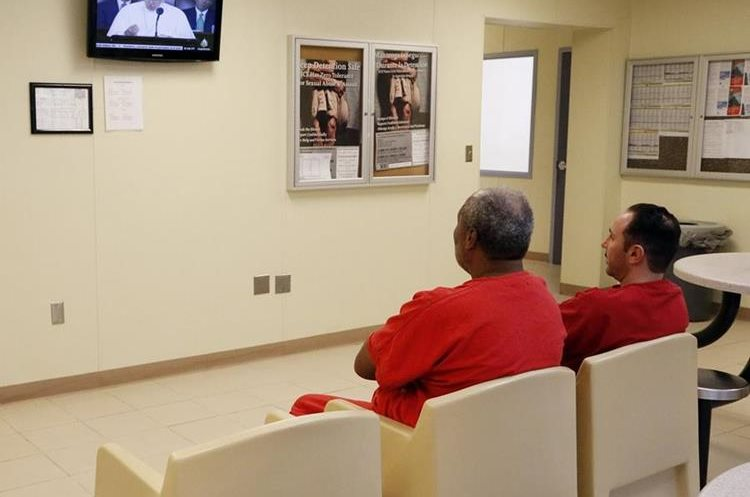Dos detenidos miran televisión en un área común del edificio de Salud Mental del Centro de Detención Krome. (Foto Prensa Libre: José A. Iglesias/El Nuevo Herald).