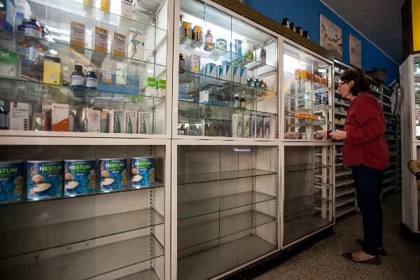 """Una empleada de la farmacia """"San Vicente"""", busca medicamentos en un estante. (EFE)."""