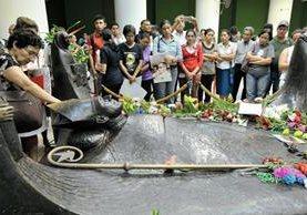Devotoa del monseñor Óscar Arnulfo Romero rodean su tumba en la catedral de San Salvador. (Foto Prensa Libre: AFP)