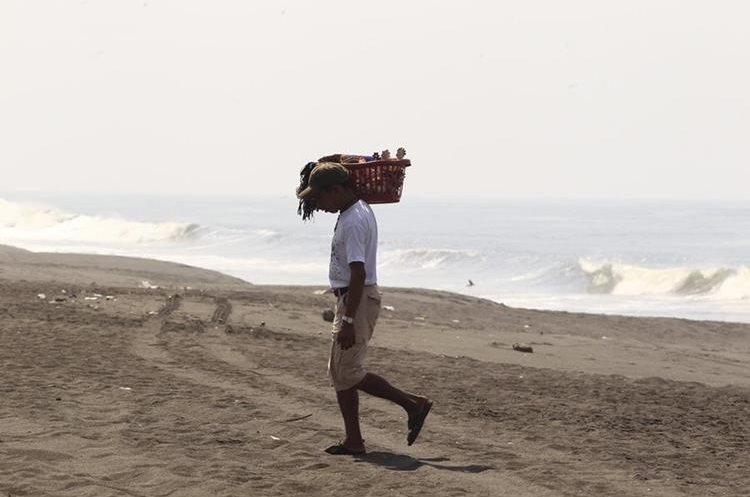 Vendedores recorren la orilla de playa para ofrecer sus productos. (Foto Prensa Libre: Carlos Hernández)
