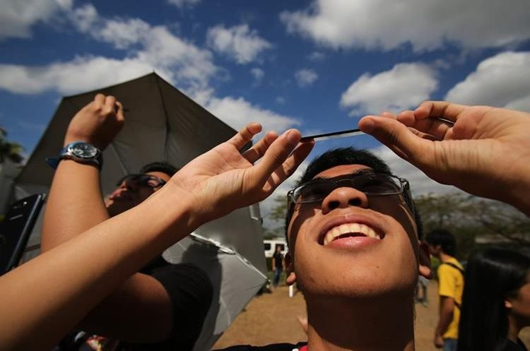 Filipino students use welders glass to view the partial solar eclipse at the University of the Philippines in suburban Quezon city, north of Manila, Philippines as it occurs Wednesday, March 9, 2016. A total solar eclipse was witnessed along a narrow path that stretched across Indonesia while in other parts of Asia a partial eclipse was visible. (AP Photo/Aaron Favila)