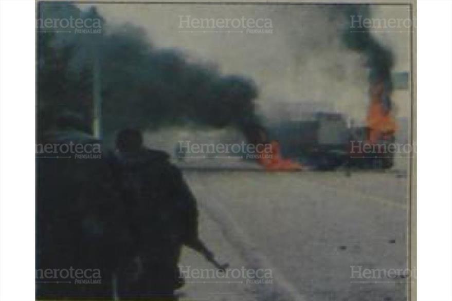 Agentes policiacos observan un camión incendiado. ( Foto: Hemeroteca PL)