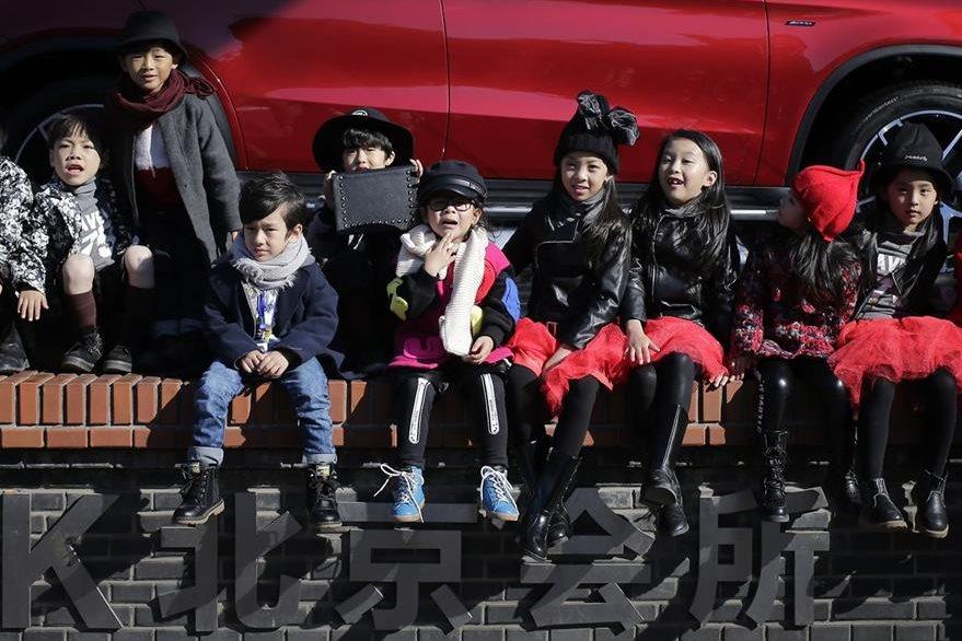 Niños chinos observan un espectáculo en una de las calles de Beijing. (Foto Prensa Libre: AP).
