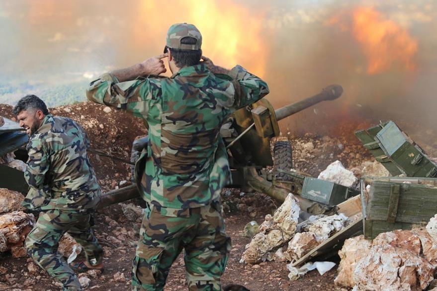 Un soldado del regimen de Bashar al Assad se tapa los oidos ante la ensordecedora explosión de los cohetes lanzados  a rebeldes. (Foto Prensa Libre: AP).