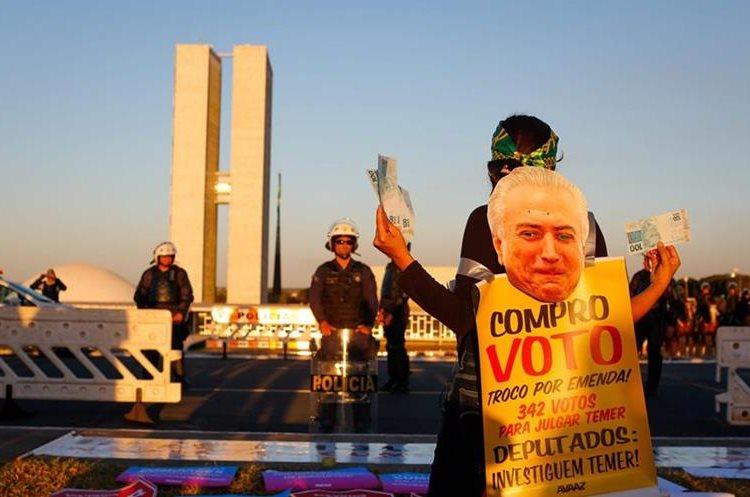 Activistas protestan contra el presidente  Temer frente a la Congreso en Brasilia. (AP).