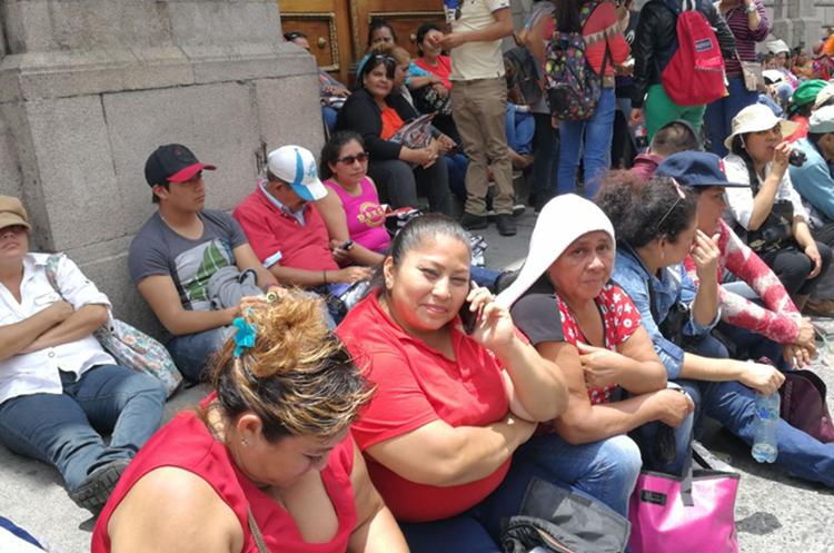 Algunos salubristas optaron por sentarse en las banquetas frente al Congreso. (Foto Prensa Libre: Érick Ávila)