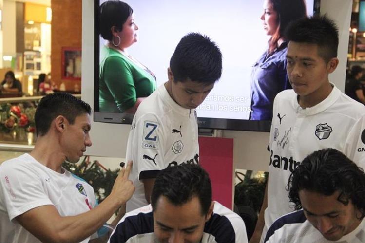 El defensa crema Carlos Gallardo firma las camisetas de los aficionados. (Foto Prensa Libre: Cremas Oficial)