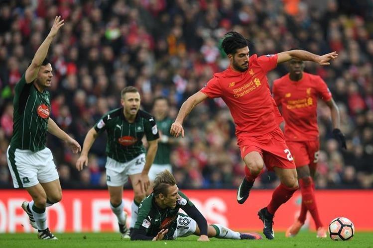 Emre Can trata de llevarse el balón ante la mirada de varios jugadores del Plymouth. (Foto Prensa Libre: AFP)
