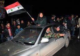 Sirios celebran en las calles de Alepo el ingreso de las fuerzas del Gobierno.