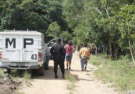 Fiscales del Ministerio Público resguardan el lugar donde ocurrió el crimen, en la aldea Machaquilá, Poptún, Petén. (Foto Prensa Libre: Walfredo Obando)
