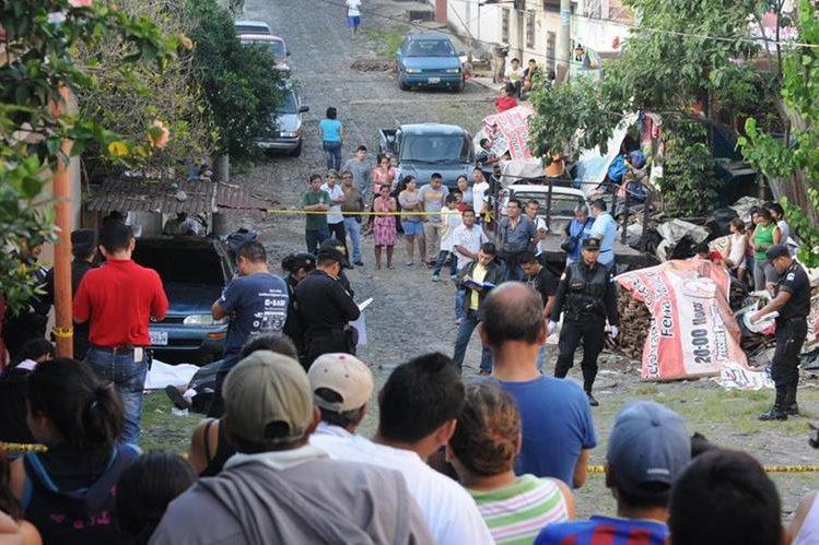 Vecinos observarn los cuerpos de la pareja asesinada este sábado en Coatepeque, Quetzaltenango. (Foto Prensa Libre: Alexander Coyoy)
