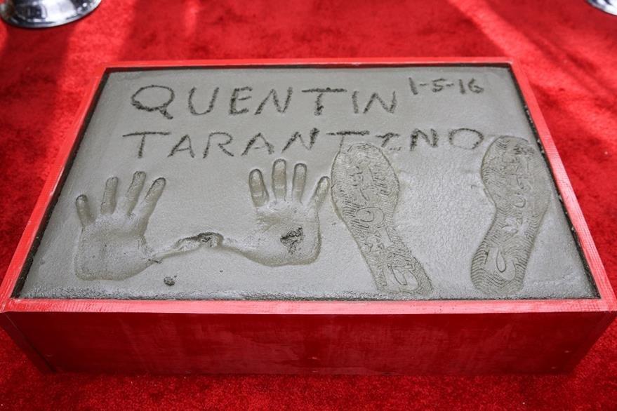 Las huellas de pies y manos de Tarantino se muestran en una ceremonia en honor a su trayectoria. (Foto Prensa Libre: AP)