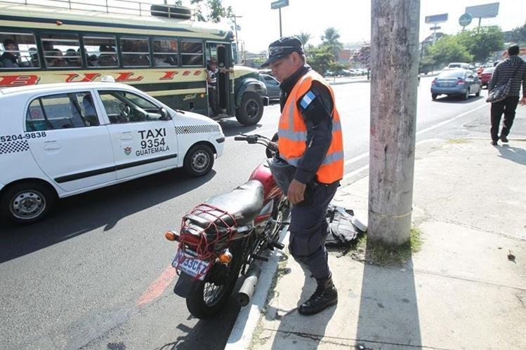 Agente de la PNC revisa una de las motocicletas usadas para cometer asalto en la calzada Roosevelt, zona 11. (Foto Prensa Libre: Erick Ávila)