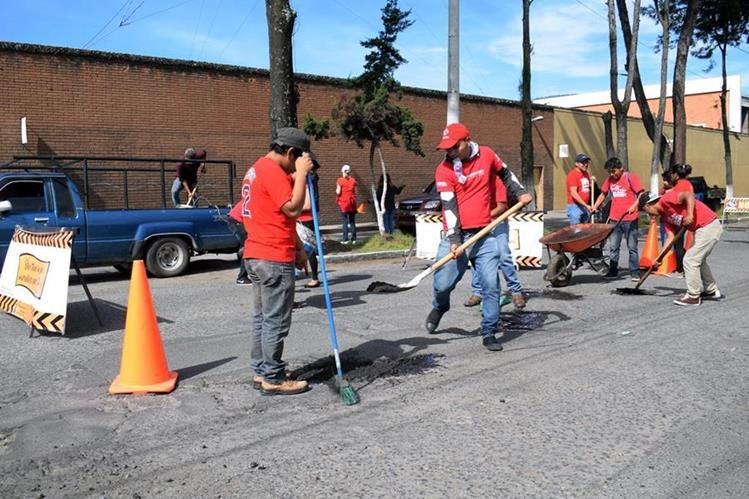 Jóvenes realizan trabajo de bacheo en la calle Rodolfo Robles, zona 3 de Quetzaltenango. (Foto Prensa Libre: Carlos Ventura)
