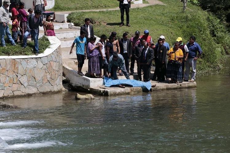 Curiosos observan el cadáver del estudiante que se ahogó en San Pedro Carchá. (Foto Prensa Libre: Eduardo Sam).