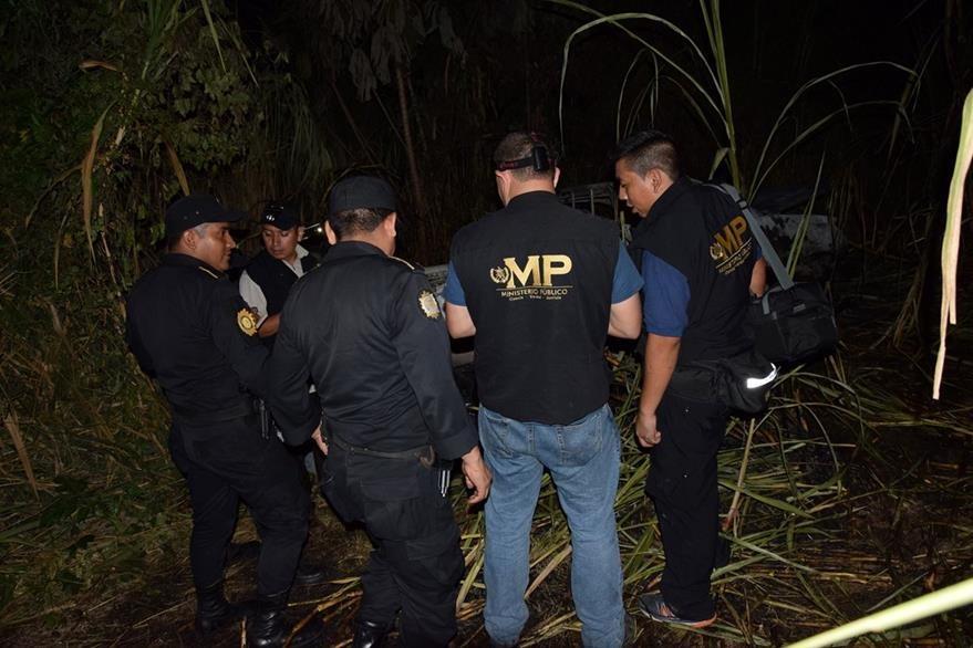 Peritos del MP recaban evidencias en Guanagazapa, Escuintla, donde fue hallado un vehículo carbonizado. (Foto Prensa Libre: Carlos E. Paredes)