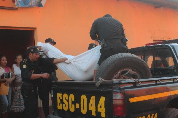 Agentes de la Policía trasladan el cuerpo de  Juan Armando López González, quien   murió baleado en Tiquisate, Escuintla, el domingo último.