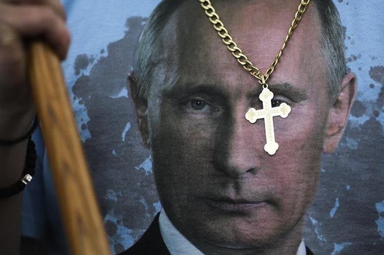 Un ruso lleva una cruz y una camisa con el retrato de Vladimir Putin en Moscú. (AP).