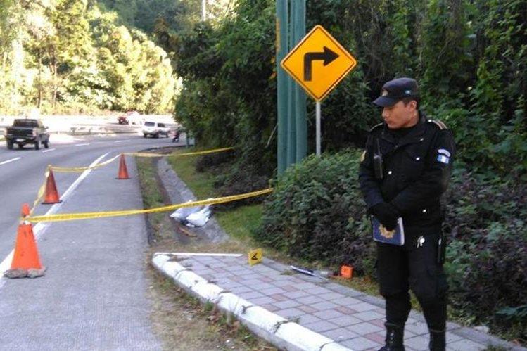 Policías resguardan escena en el kilómetro 24 de la ruta Interamericana, lugar en el que fue encontrado el cadáver. (Foto Prensa Libre: Estuardo Paredes)