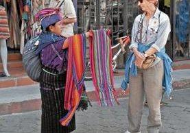 Una vendedora de Sololá, donde viven las mujeres más bajas de Guatemala, ofrece sus productos a una turista, lo que deja en evidencia la diferencia de estatura de las guatemaltecas con las mujeres extranjeras. (Foto Prensa Libre: Ángel Julajuj)