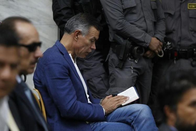 Juan de Dios Rodríguez lee la Biblia mientras espera la audiencia en la Sala de Vistas de la CSJ. (Foto Prensa Libre: Paulo Raquec)