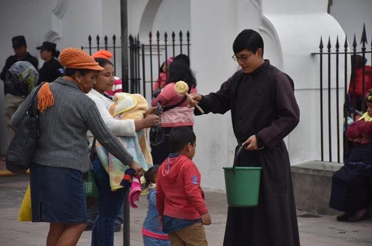 Un sacerdote bendice a una familia, luego de haber participado en la santa eucaristía.(Foto Prensa Libre: Mario Morales)
