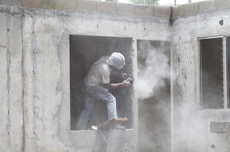 Albañil trabajo en retoques estéticos de viviendas que se terminaron de fundir la semana pasada. (Foto Prensa Libre: Erick Ávila)