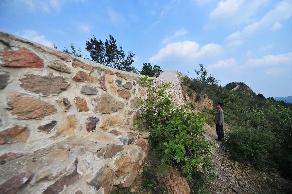 Un poblador muestra la remodelación de una sección de la Gran Muralla de China. (AFP)