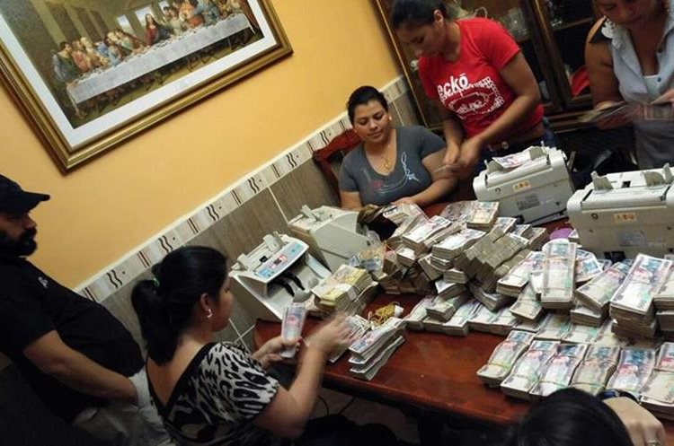 "Handout photo released by the Honduran Criminal Investigation Technical Agency (ATIC) of ATIC members counting money seized to the Salvatrucha gang in the Avalanche operation in San Pedro Sula, 240 km of Tegucigalpa on February 23, 2016. Honduran authorities looking for new ways to combat gangs terrorizing the country are waging an operation called ""Avalanche"" to seize bank accounts, properties and even a small hospital from wealthy crime bosses. The police operation, which began February 23, is continuing with no defined end date.  AFP PHOTO / Honduran Criminal Investigation Technical Agency (ATIC)"