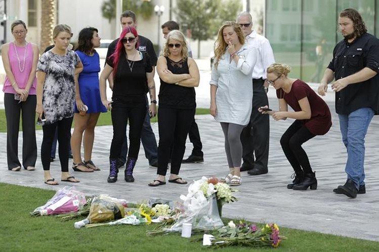 Un grupo de personas coloca flores en un lugar cercano a la discoteca Pulse, donde el domingo en la madrugada ocurrió la masacre. (Foto Prensa Libre: AP).