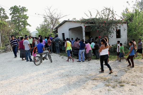 Pobladores de  Poptún, Petén, observan la vivienda donde fue atacada una familia y murieron tres. (Foto Prensa Libre: Walfredo Obando)