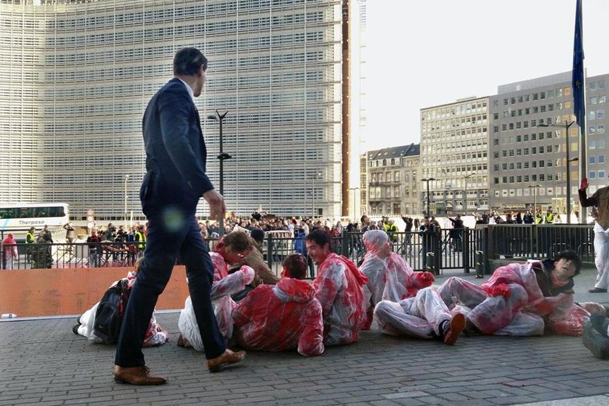 Manifestantes pintaron su ropa de rojo y protestaron este domingo contra la firma del CETA, el acuerdo comercial entre Canadá y la Unión Europea. (Foto Prensa Libre: EFE)