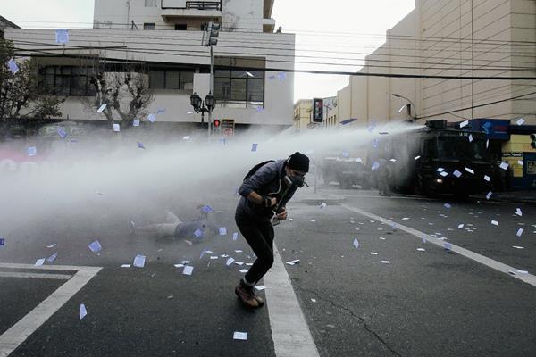 Manifestantes son dispersados con agua por las autoridades chilenas. (Foto Prensa Libre:EFE)