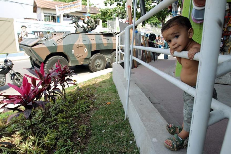 Un niño observa un operativo  policial en el complejo de favelas  Alemao, Brasil. (Foto Prensa Libre: EFE).