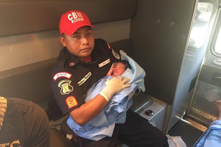 La familia y los socorristas celebran el alumbramiento dentro de la ambulancia (Foto Prensa Libre: Bomberos Municipales)