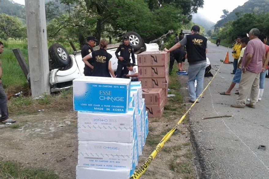 Agentes de la PNC contabilizan cigarrillos localizados en un picop accidentado en Poptún. (Foto Prensa Libre: Walfredo Obando)