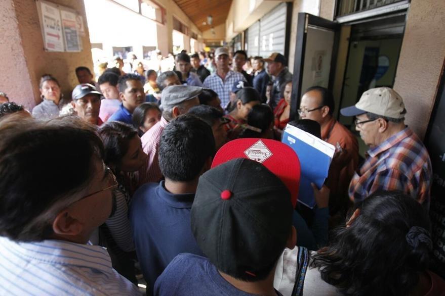 Decenas de personas consultan sobre el trámite de emisión de pasaportes, luego de ser suspendido temporalmente. (Foto Prensa Libre: Paulo Raquec)