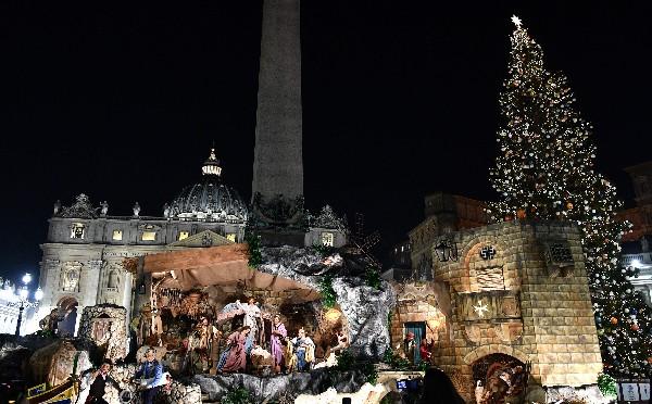El árbol de Navidad (d) y el belén (c) se exhiben en la plaza de San Pedro. (AFP).
