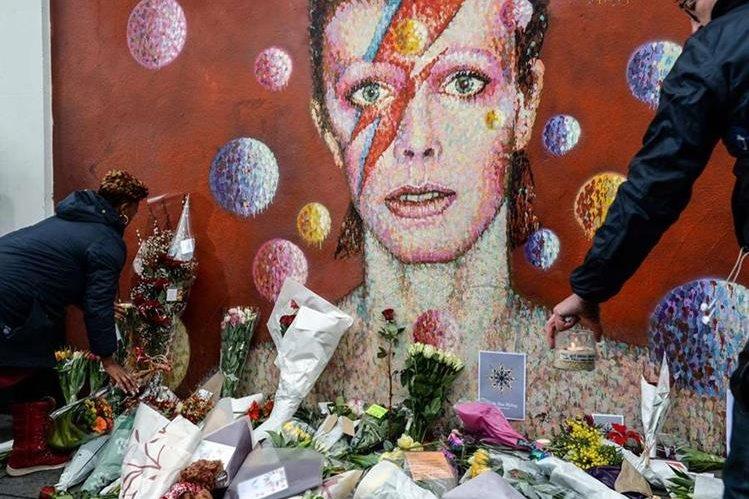 Flores y velas se colocan junto a una acuarela del fallecido cantante británico David Bowie en un altar improvisado por sus seguidores en Brixton, Londres. (Foto Prensa Libre: AFP)